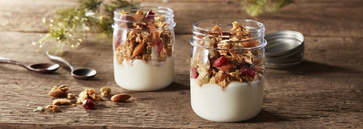 Two small, glass jars filled with yogurt and topped with Morning Summit cereal